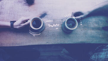 two friends holding coffee cups